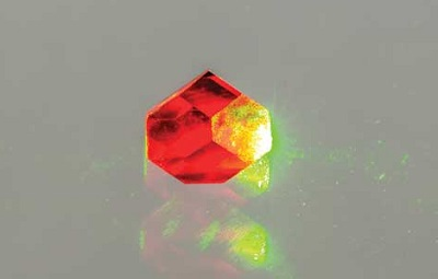 A photo of a reddish-coloured diamond with NV centres being illuminated with a green-yellow laser beam