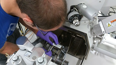 A photograph of a student at University of Manchester mounting the Deben Microtest stage in a FEI Quanta 650 SEM. Courtesy Deben.