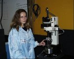 Alexandra Imre next to the magnetic force microscope (MFM) used to image the logic devices.