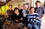 Georgia Tech researchers pose with equipment used to demonstrate entanglement of qubits.