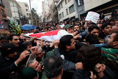 Mourners carry the Iranian flag-covered body of a murdered physicist
