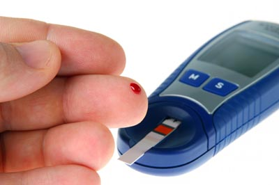 A diabetic doing a glucose level finger blood test