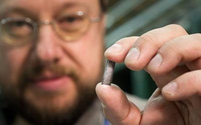 Detlef Kuchler, a physicist in CERN's beams department, holds a piece of the lead source material used to create heavy ions for the LHC. (Courtesy: M Brice/CERN)