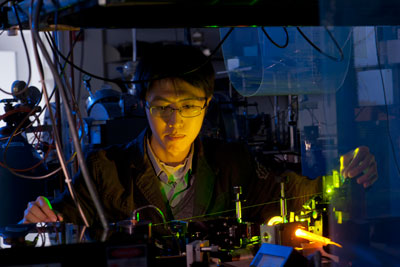 Photo of Rice University graduate student Shuzhen Ye using an ultraviolet laser to create a Rydberg atom