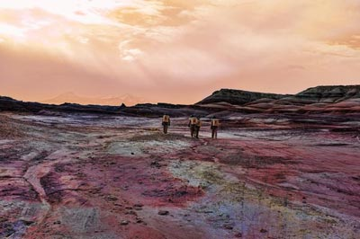 Photograph of people in simulated space suits walking across a desert landscape
