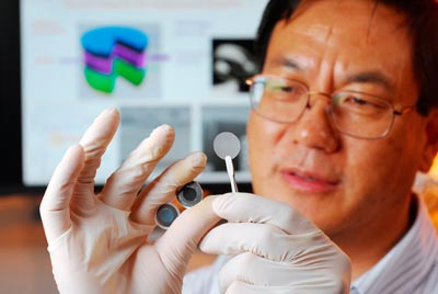 Photograph of Zhong Lin Wang holding the components of a new self-charging power cell