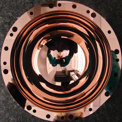 Photo of a concave copper hemisphere, with bolt holes around its rim, which is so shiny it reflects the camera and photographer